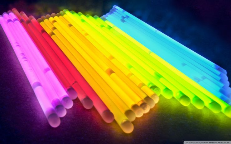 a row of rainbow colored glow stickes in a dark background