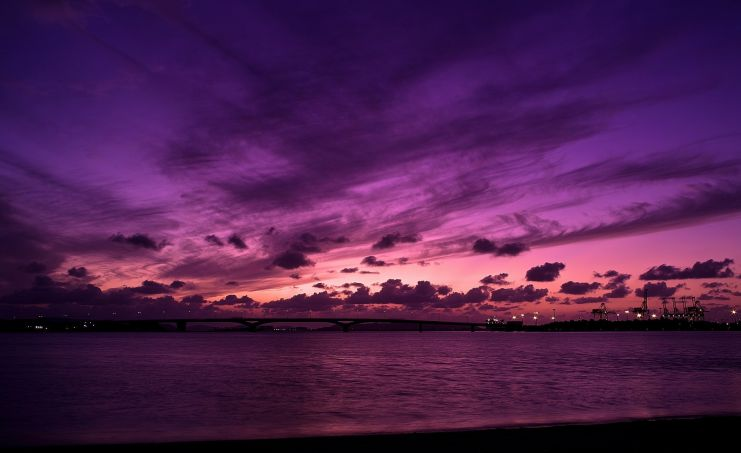 a picture of a pink to purple sunset with clouds