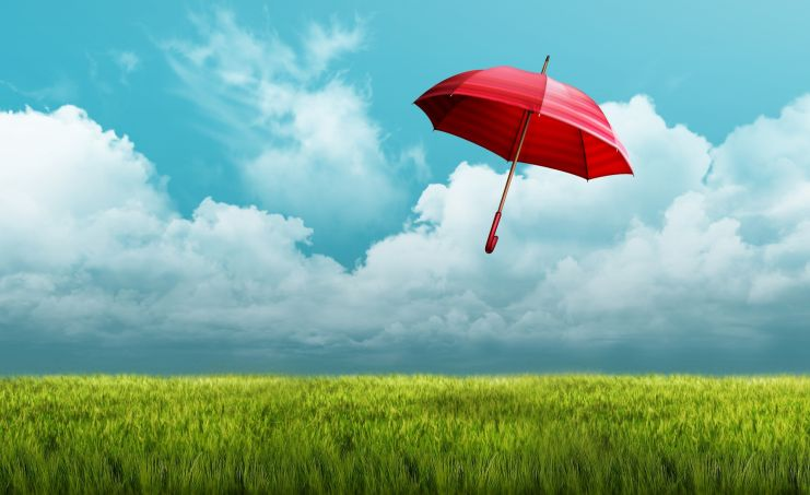 A blue sky and a green field with a red umbrella floating through the air
